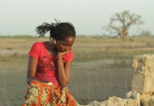 Coumba sits thinking in a scene from Tall as the Baobab Tree.